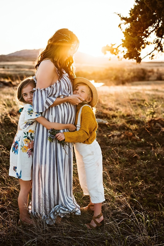 Family Photography, mother with her two kids standing in a grassy field