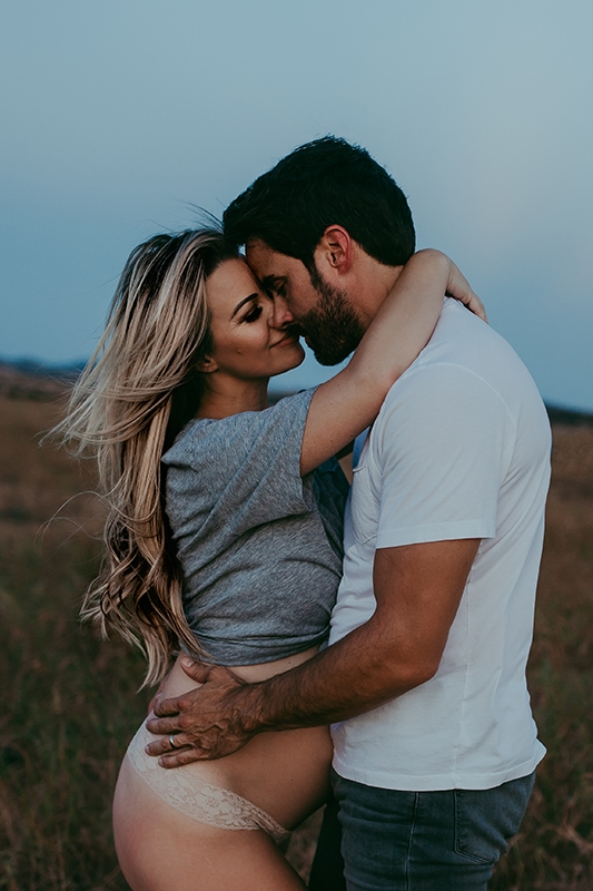 Family photography, husband and pregnant wife standing in a field together nose to nose