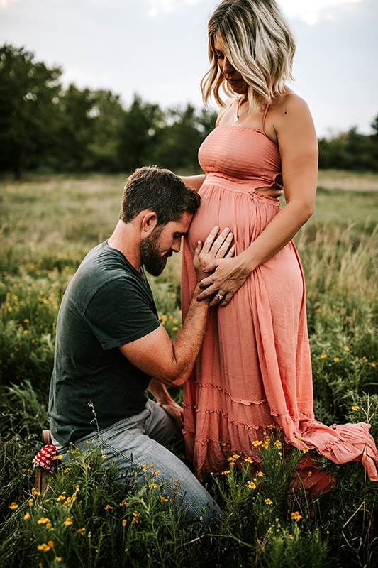 Family photography, husband kneeling with his head on his pregnant wife's belly