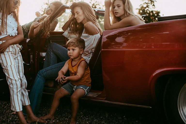 Family photography, mother and children sitting together in old car