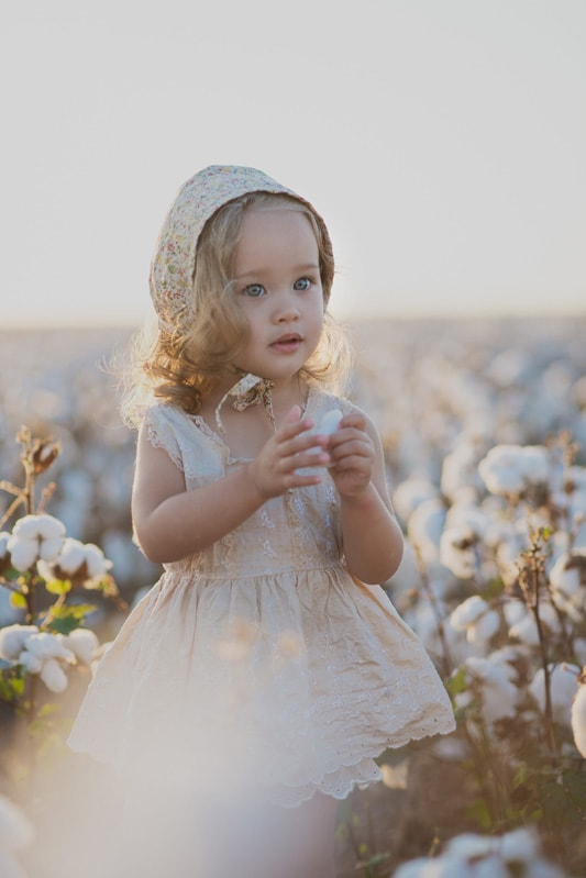 Family Photography, close up of little girl in bonnet standing in a field of cotton