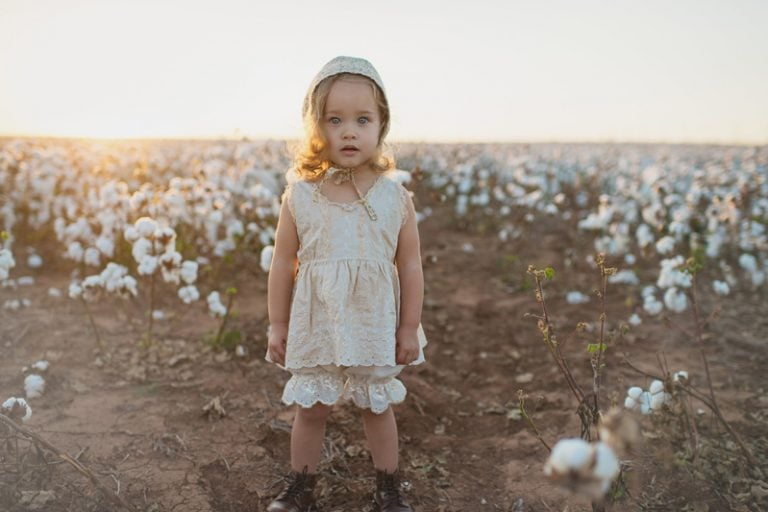 Family Photography, little girl in bonnet standing in a field of cotton