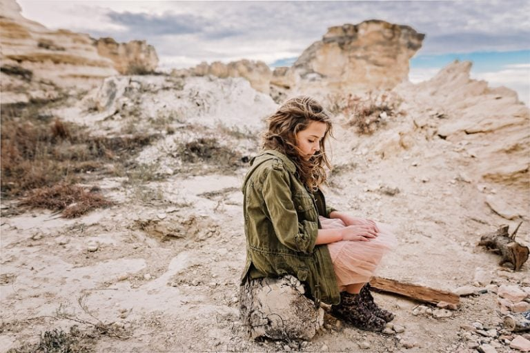 Family Photography, young girl sitting on a rock in the desert