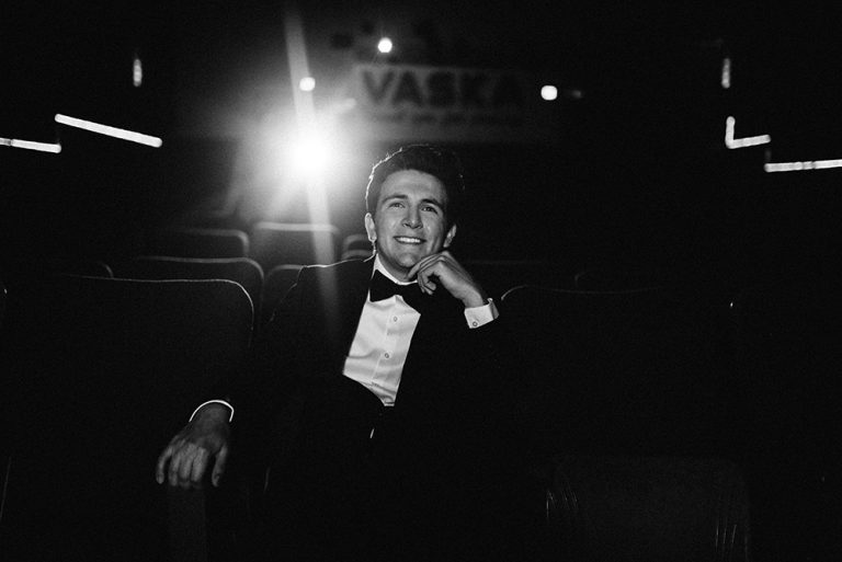 Family photography, man in tux sitting inside theater