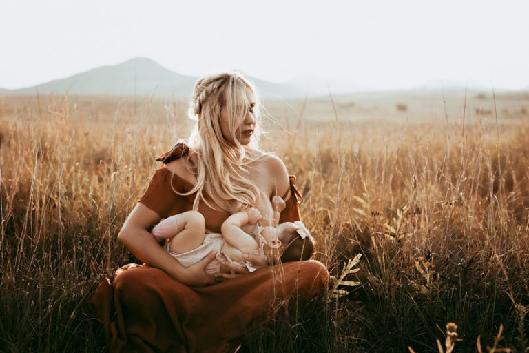 Family Photography, woman breastfeeding in a field
