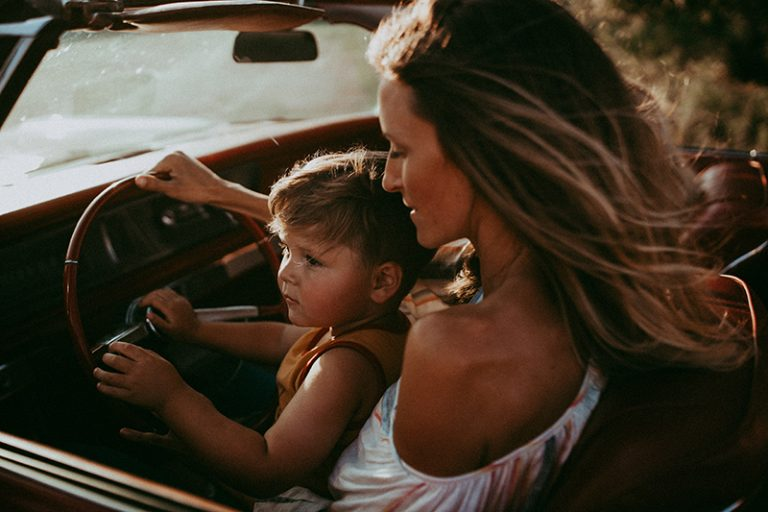 Family photography, mother siting with son in the drivers seat of car