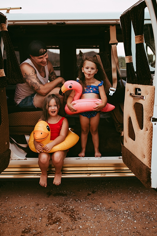 Family photography, father with daughters in swimsuits and floats getting out of a VW van