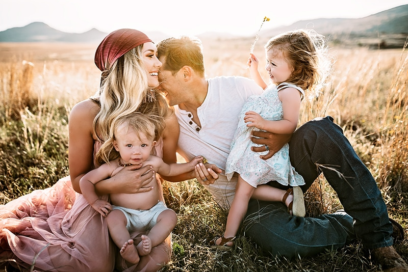 Family Photography. family of 4 sitting in tall grass with husband kissing wife's shoulder