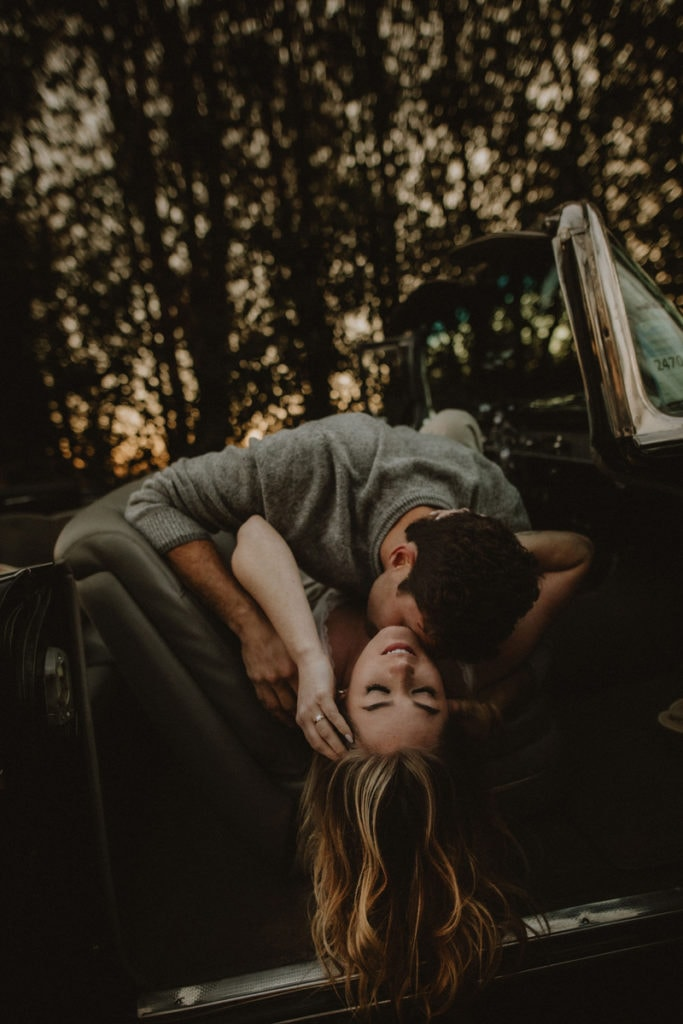 Family Photographer, man kissing woman's neck as she lays in the backseat of an old car