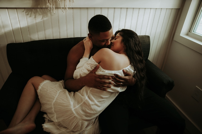 Family Photographer, couple kissing on dark color couch
